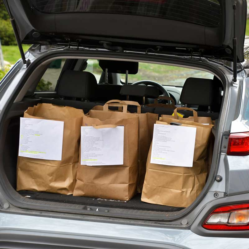Food deliveries loaded in cars